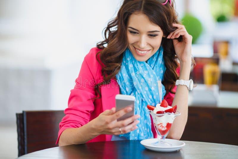 Den unga kvinnan äter efterrätten och samtal på telefonen royaltyfria bilder