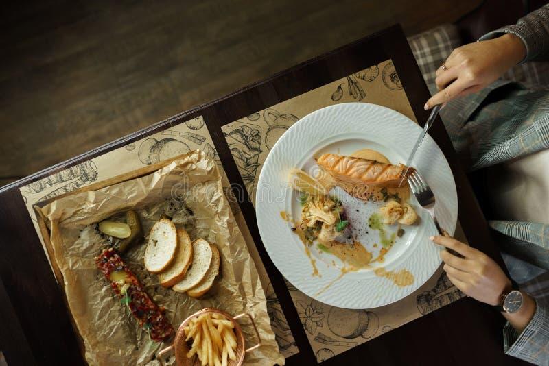 Den unga kvinnan äter laxfilén och fiskar tartare på en elegantly lagd tabell i en restaurang white för studio för makro för häls royaltyfri fotografi