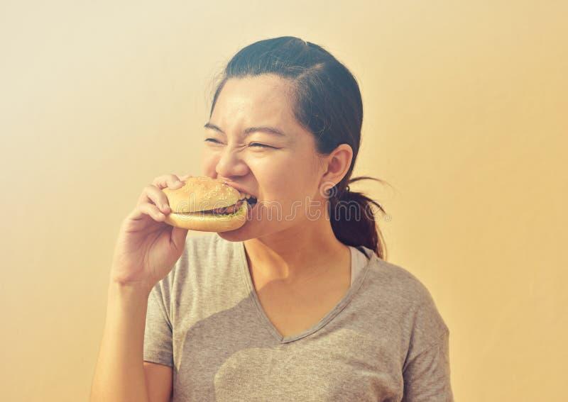 Den unga kvinnan äter skräpmathamburgaren i hand royaltyfria foton