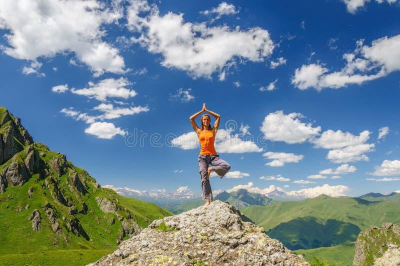 Den unga kvinnan övar yoga i bergen arkivbild