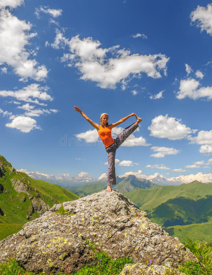 Den unga kvinnan övar yoga i bergen royaltyfria bilder