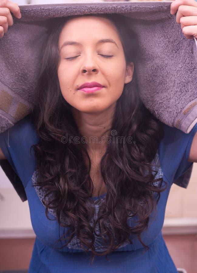 Den unga kvinnan andas mycket starkt ångan runt om henne och att cleanning perioder av framsidabehandling arkivbild