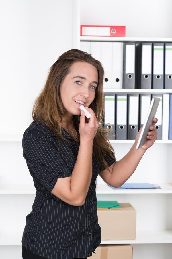 Den unga kvinnan använder en minnestavla som sminkspegeln royaltyfri foto
