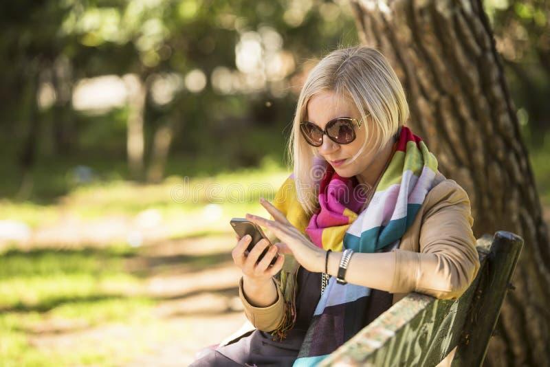 Den unga kvinnan använder smartphonesammanträde på bänk i parkera royaltyfria bilder