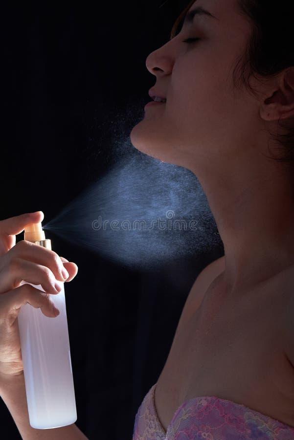 Den unga kvinnan applicerar doft arkivbild