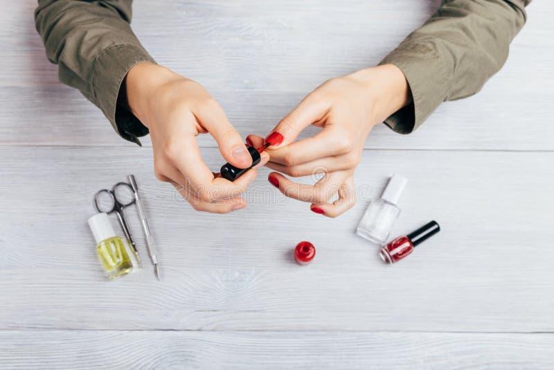 Den unga kvinnan applicerar rött polermedel på spets av spikar till att försegla hennes mani arkivfoto