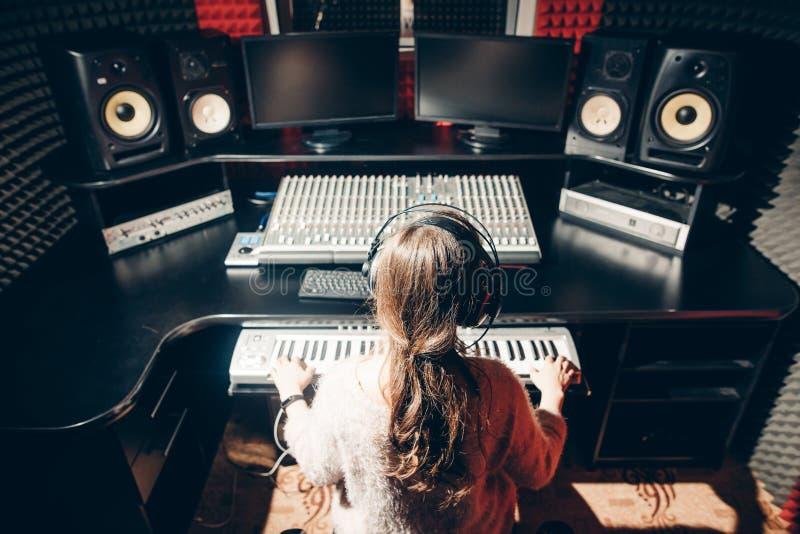 Den unga kvinnan arbetar i musikstudion royaltyfri bild
