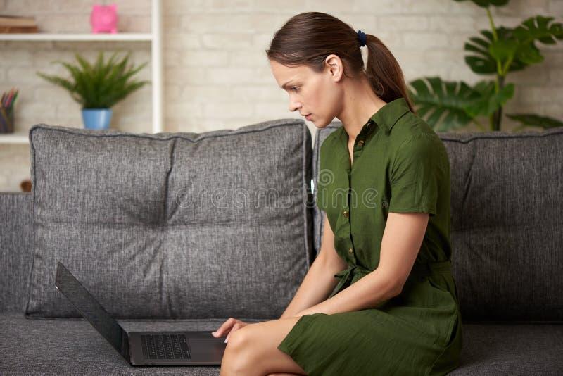 Den unga kvinnan arbetar med bärbar datordatoren som sitter på en soffa arkivfoton