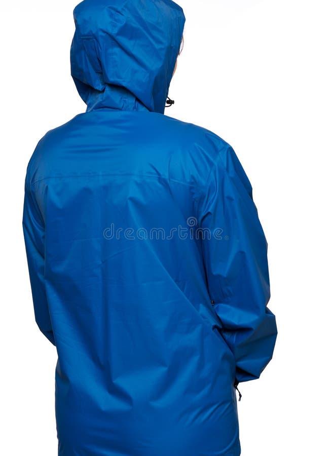 Den unga kvinnan bär den blåa regnrocken med huven royaltyfri fotografi