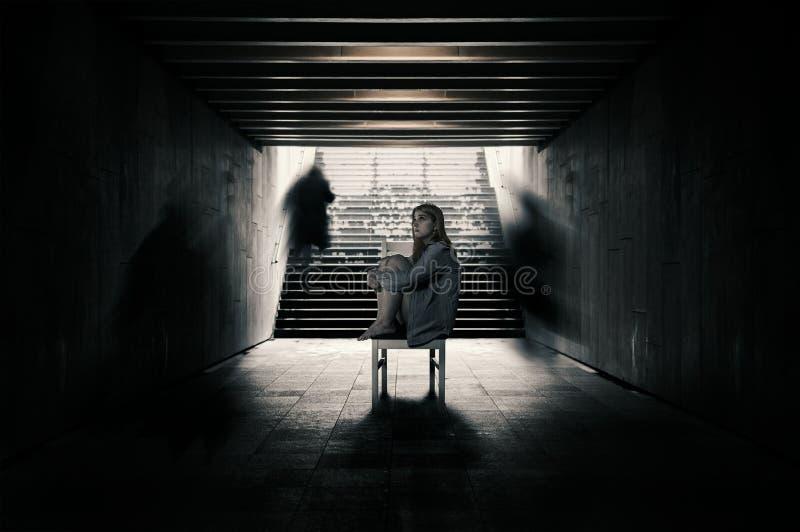 Den unga kvinnan bara i en tunnel och främlingar passerar bortom royaltyfria foton