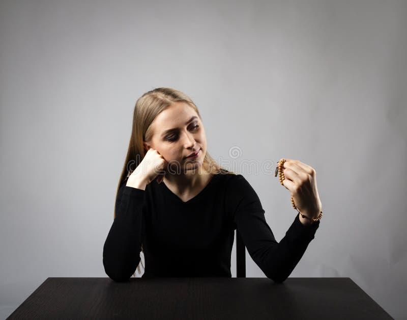 Den unga kvinnan ber med radbandpärlor arkivfoton