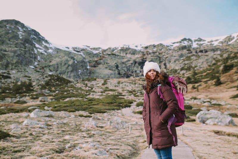 Den unga kvinnan beskådar de snöig bergen royaltyfria bilder