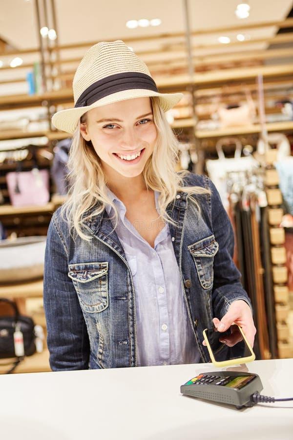 Den unga kvinnan betalar cashless med smartphonen app arkivbild