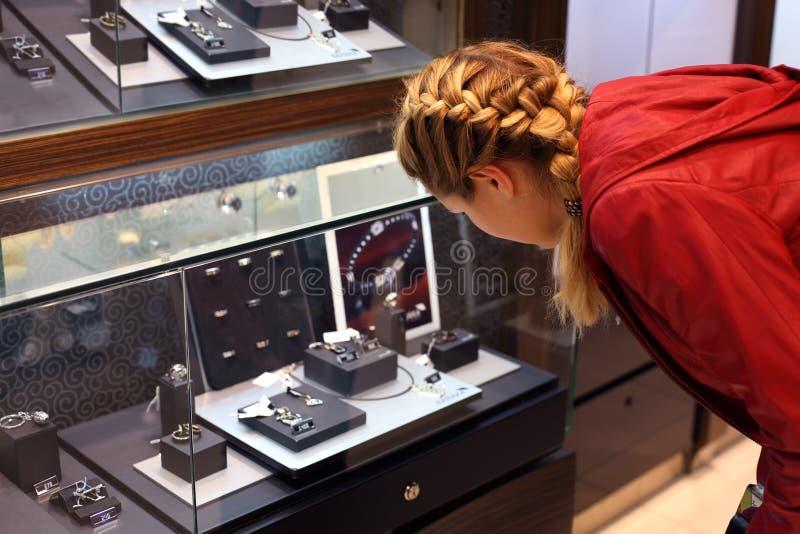 Den unga kvinnan betraktar smycken i ett smyckenlager. royaltyfria bilder