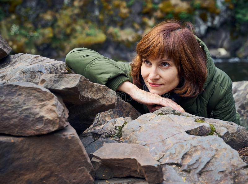 Den unga kvinnan beundrar den nordliga naturen Personen på bakgrund av vaggar, stenar, lös skog arkivbilder