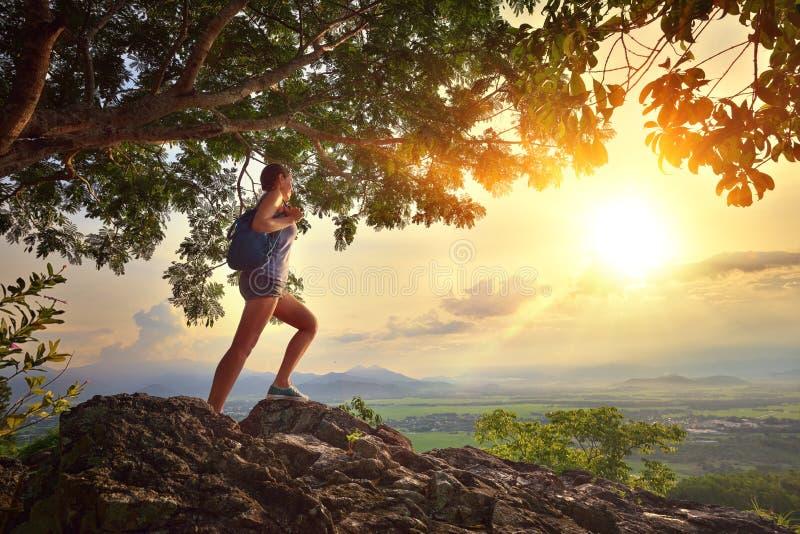 Den unga kvinnan beundrar solnedgången med ett ryggsäckanseende på klippan arkivfoto