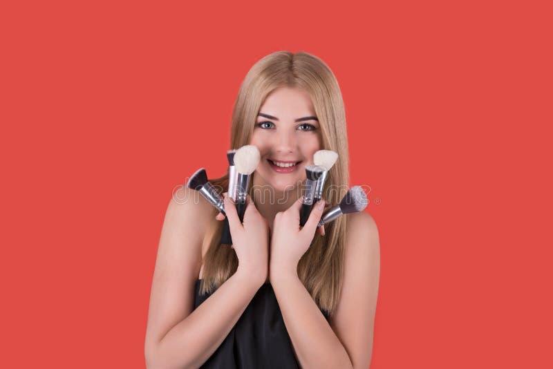 Den unga kvinnan blondinen med olika borstar för ett smink royaltyfri fotografi