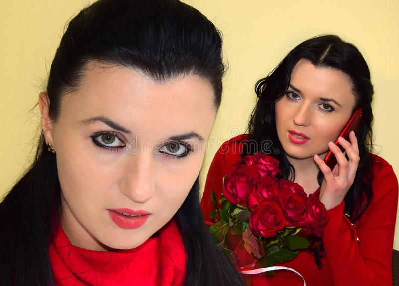 Den unga kvinnan brunetten är iklädd en röd klänning Kvinnan rymmer en bukett av röda rosor i hand och talar vid den mobila phen fotografering för bildbyråer