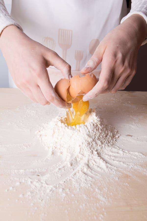Den unga kvinnan bryter ägget ovanför vitt mjöl för att göra deg för italiensk pasta, för ravioli eller klimpar royaltyfri fotografi