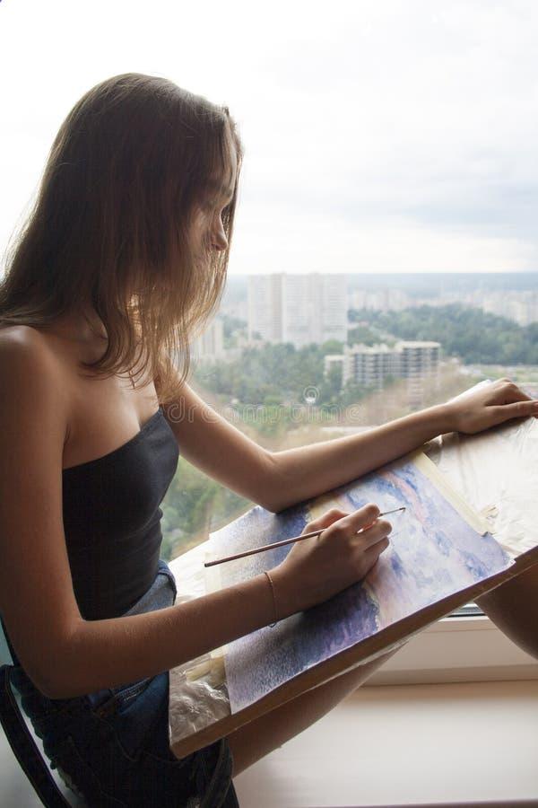 Den unga kvinnan drar en vattenfärgmålning på papper Den kvinnliga konstnären målar akvarelllandskap stock illustrationer