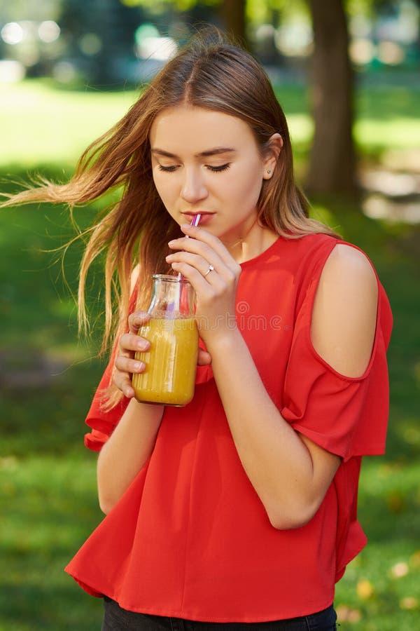 Den unga kvinnan dricker den sunda detoxsmoothien royaltyfri bild