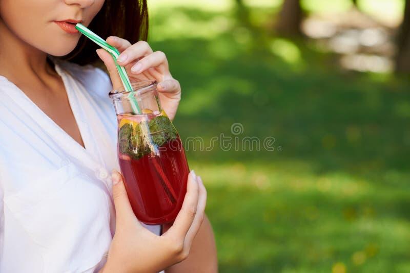 Den unga kvinnan dricker sunt detoxte arkivfoto