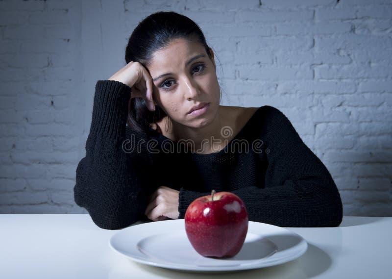Den unga kvinnan eller tonårig seende äpplefrukt på maträtt som symbol av galet bantar i näringoordning arkivfoton