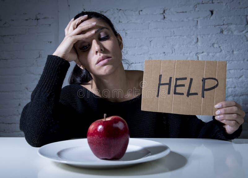 Den unga kvinnan eller tonårig seende äpplefrukt på maträtt som symbol av galet bantar i näringoordning arkivfoto