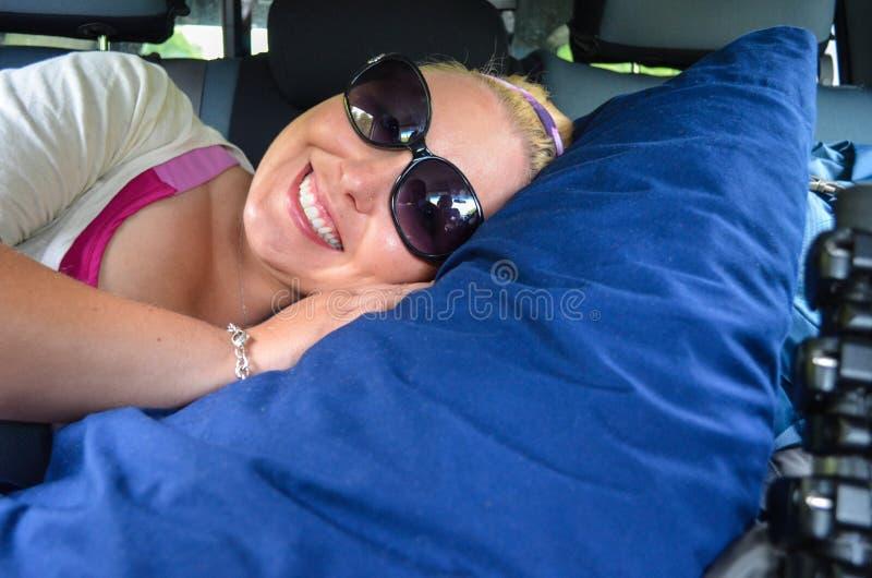 Den unga kvinnan får bekväm i backseaten av en bil, med en stor kudde som är klar att ta sig en tupplur på en tur för lång väg royaltyfria foton