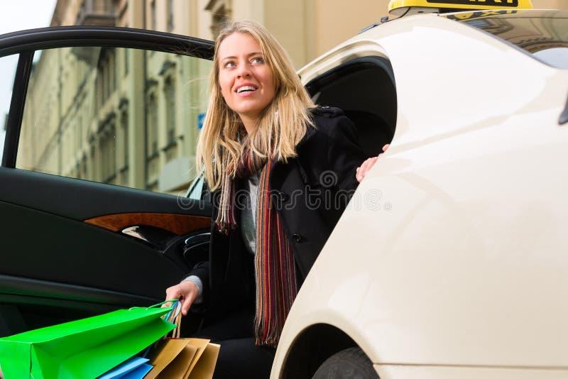Den unga kvinnan får ut ur taxar fotografering för bildbyråer