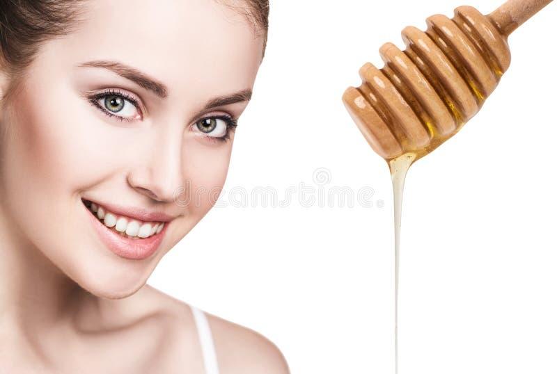 Den unga kvinnan förbereder sig för ansikts- maskering för honung arkivbilder