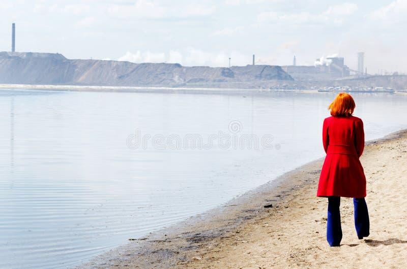 Den unga kvinnan går bara på en strand royaltyfri fotografi