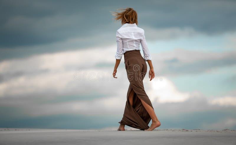 Den unga kvinnan går barfota i öken på himmelbakgrund tillbaka sikt arkivfoto