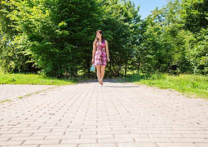 Den unga kvinnan går barfota på trottoaren arkivbild