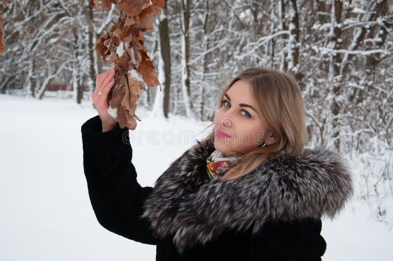 Den unga kvinnan går i vinter i skogen och ser upp äntligen sidor för års` s arkivbild