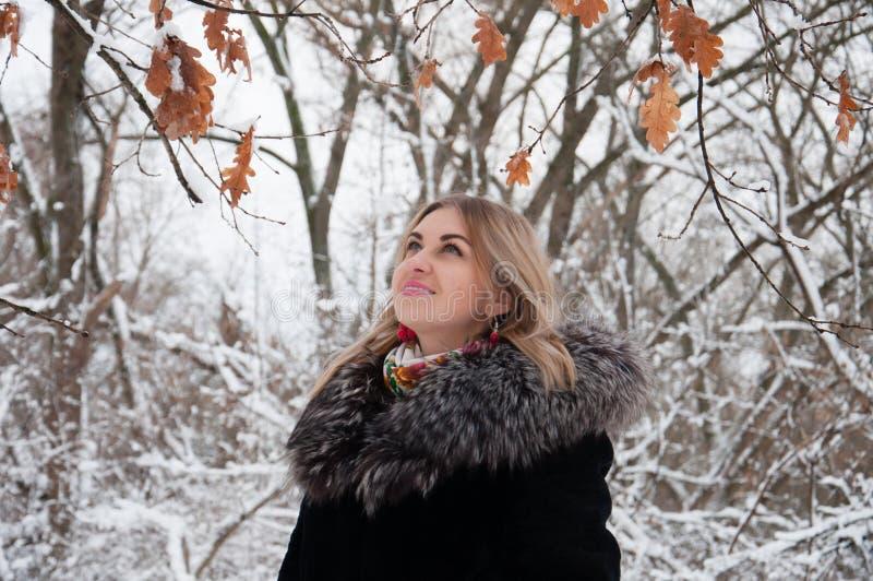 Den unga kvinnan går i vinter i skogen och ser upp äntligen sidor för års` s arkivfoto