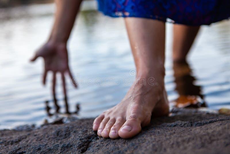 Den unga kvinnan går ut ur vattnet, medan trycka på vattnet med hennes hand fotografering för bildbyråer