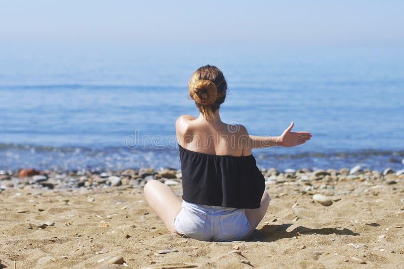Den unga kvinnan gör meditation i lotusblomma att posera på havet/havstranden, harmoni och begrundande Praktiserande yoga för här royaltyfri fotografi