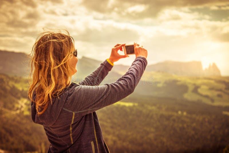 Den unga kvinnan gör selfiefotoet i fjällängarna, Dolomites, Italien arkivbild
