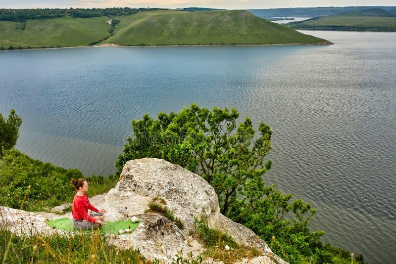 Den unga kvinnan gör yogaövningar på vagga ovanför den härliga floden royaltyfria bilder
