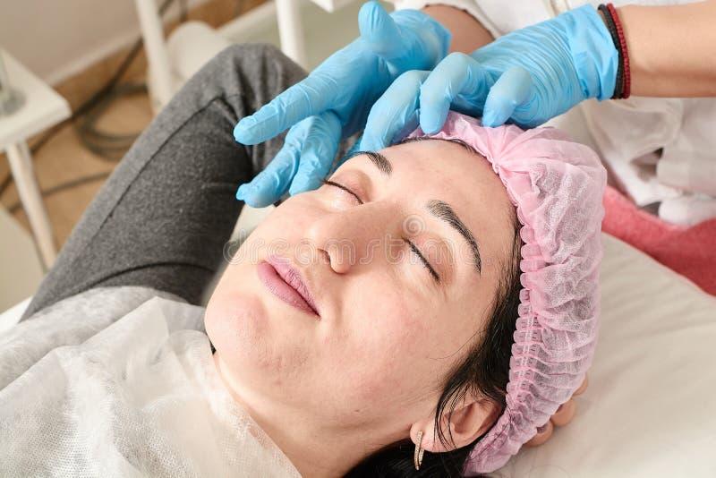 Den unga kvinnan g?r yrkesm?ssig ansikts- massage i sk?nhetsalongen royaltyfri fotografi