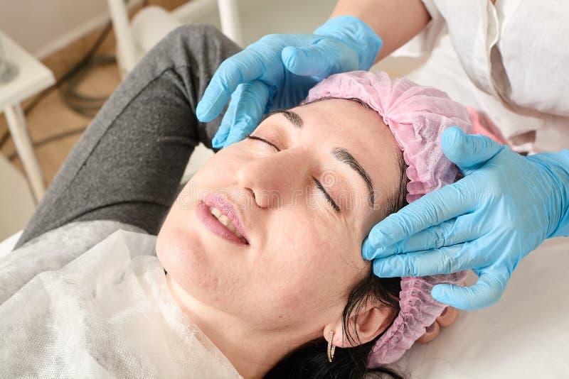 Den unga kvinnan g?r yrkesm?ssig ansikts- massage i sk?nhetsalongen royaltyfri bild