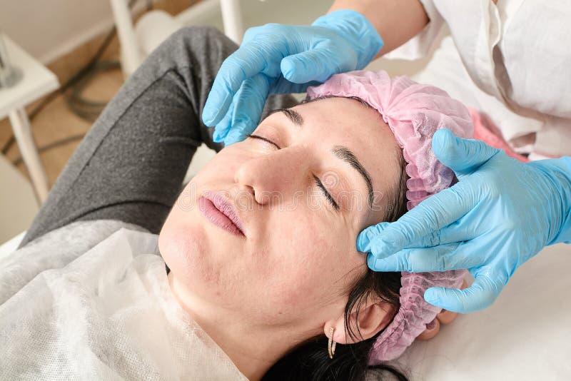 Den unga kvinnan g?r yrkesm?ssig ansikts- massage i sk?nhetsalongen arkivbild