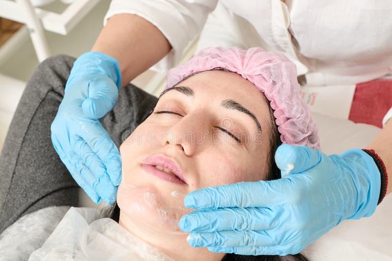Den unga kvinnan g?r yrkesm?ssig ansikts- massage i sk?nhetsalongen royaltyfri foto
