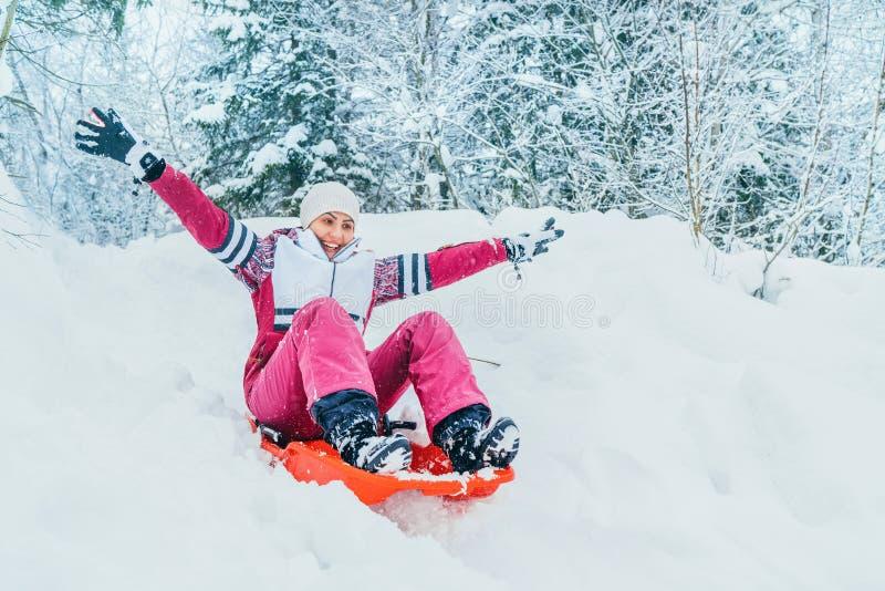 Den unga kvinnan glider ner från snölutningen som sitter i en glidbana Bild för vinteraktivitetsbegrepp arkivfoton