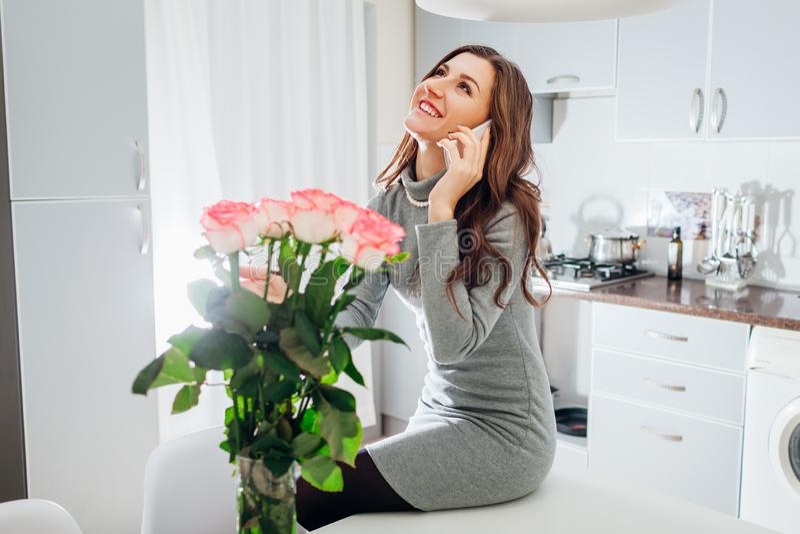 Den unga kvinnan grundar buketten av rosor på kök, och kalla maken för att säga tacka dig Lyckligt upphetsat le för flicka arkivfoton