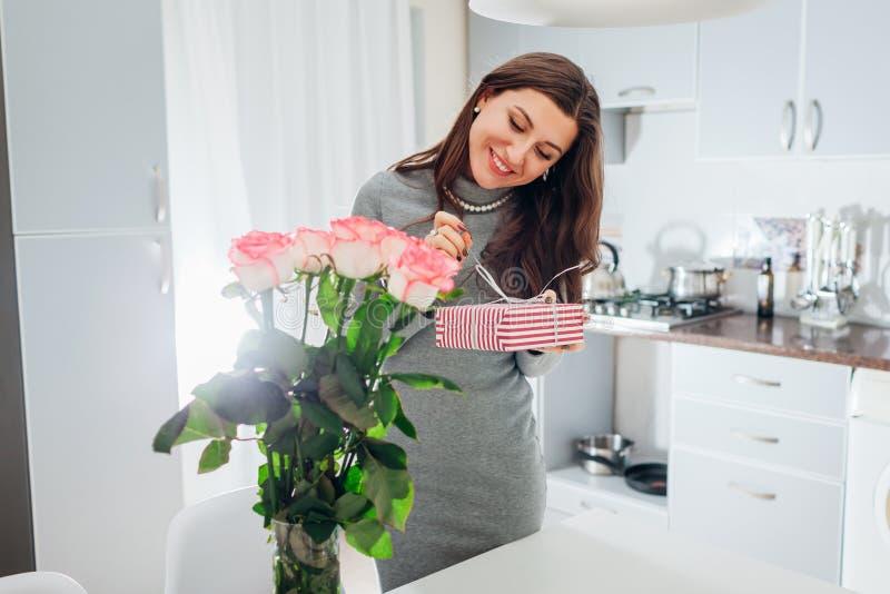 Den unga kvinnan grundar gåvaasken och buketten av rosor på kök Lycklig le öppnande gåva för flicka arkivfoto