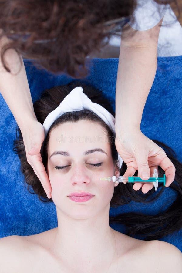 Den unga kvinnan har en ansikts- injektion på hennes framsida som ser mer ung och mindre tröttad fotografering för bildbyråer