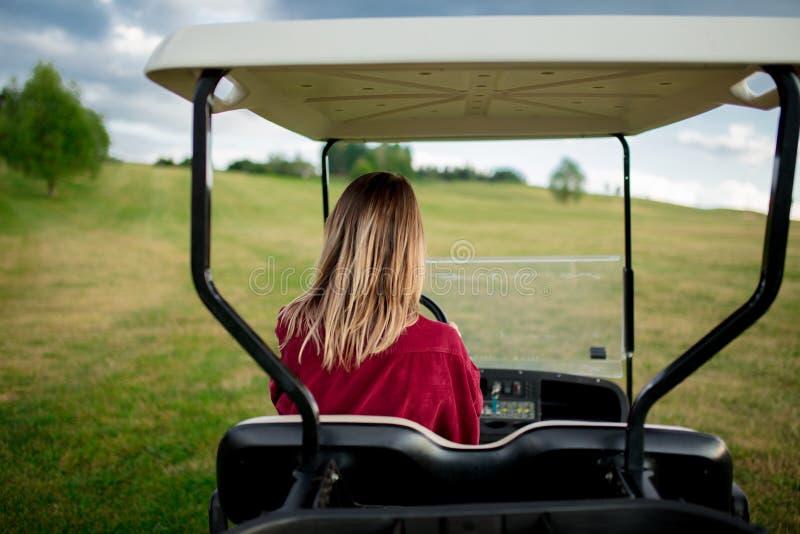 Den unga kvinnan har en gyckel med golfbarnvagnbilen på ett fält i berg royaltyfri bild