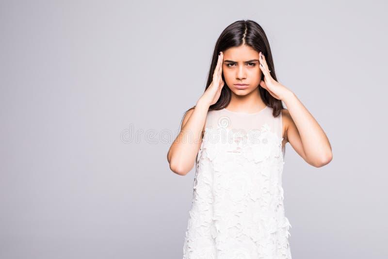 Den unga kvinnan har huvudvärken som isoleras på grå bakgrund arkivbild